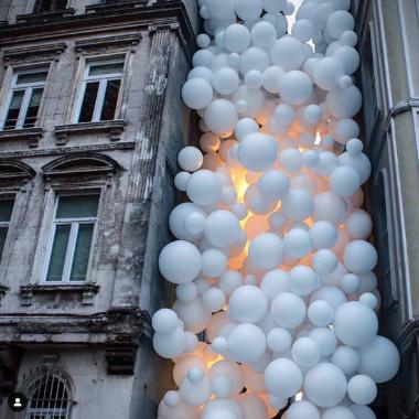balti balionai su apšvietimu tarp pastatų